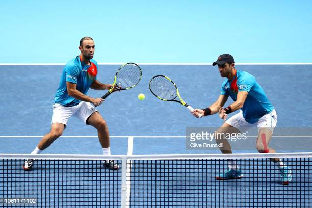 Juan Sebastian Cabal of Columbia and partner Robert Farah of Columbia return the ball during their doubles round robin match against Jamie Murray of...