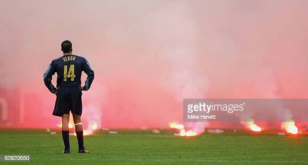 Juan Sebastian Veron of Inter Milan looks on as Inter fans shower the pitch with flares during the UEFA Champions League quarterfinal second leg...