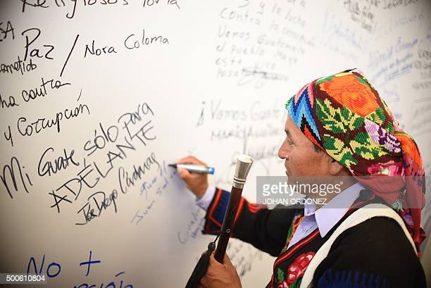 Juan Sen member of the local indigenous community writes a sentence against corruption on a wall during events marking the International...