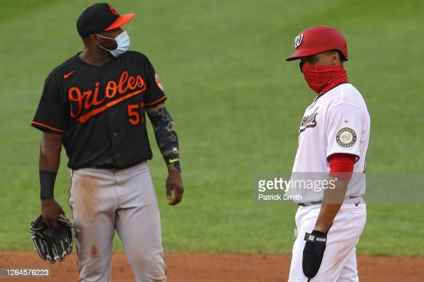 Juan Soto of the Washington Nationals and Hanser Alberto of the Baltimore Orioles both wear face-coverings after Soto hit a double during the fourth...