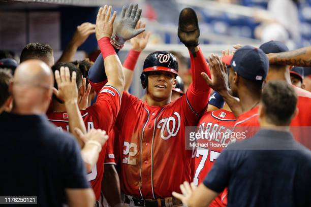 Juan Soto of the Washington Nationals celebrates with teammates after scoring a run in the tenth inning against the Miami Marlins at Marlins Park on...