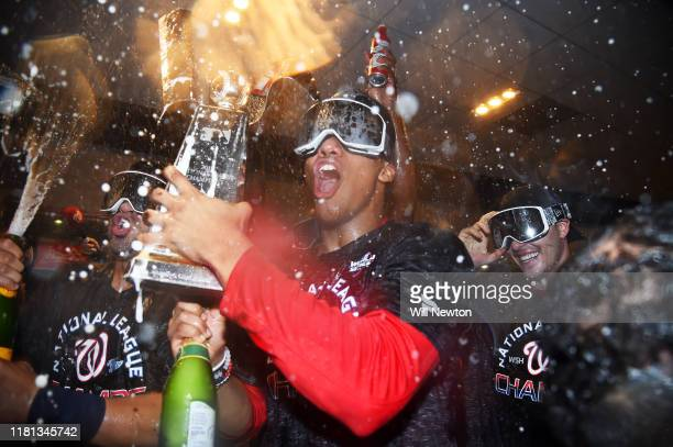 Juan Soto of the Washington Nationals celebrates with the trophy and teammates in the clubhouse after they won game four and the National League...