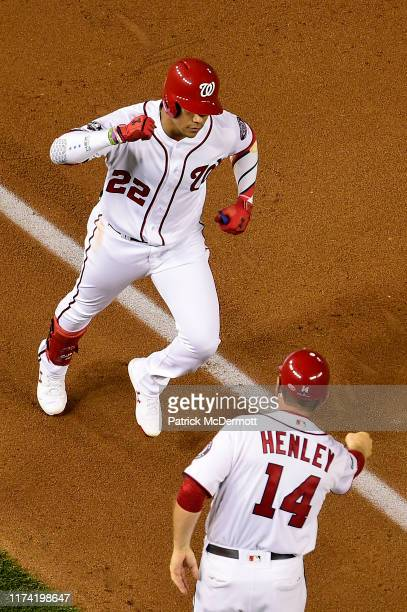 Juan Soto of the Washington Nationals celebrates with third base coach Bob Henley as he runs the bases after hitting a tworun home run in the first...