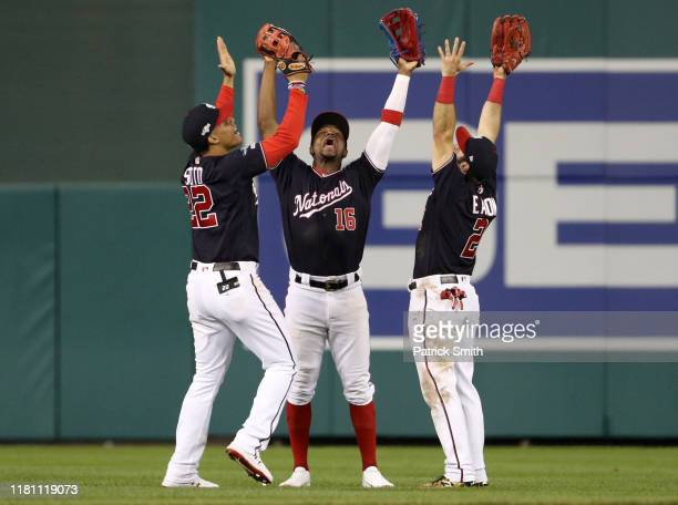 Juan Soto, Victor Robles, and Adam Eaton of the Washington Nationals celebrate defeating the St. Louis Cardinals 8-1 after game three of the National...