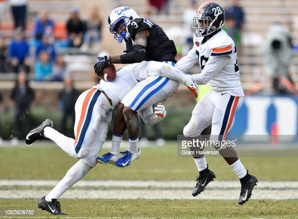 Juan Thornhill and Brenton Nelson of the Virginia Cavaliers tackles T.J. Rahming of the Duke Blue Devils after a catch during their game at Wallace...