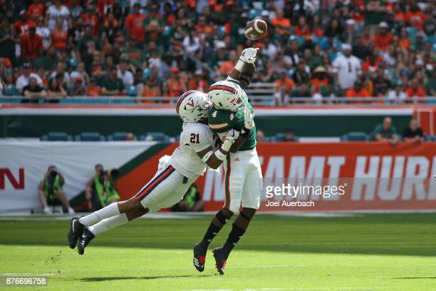 Juan Thornhill of the Virginia Cavaliers causes an interception after he tips the ball away form Jeff Thomas of the Miami Hurricanes on November 18,...