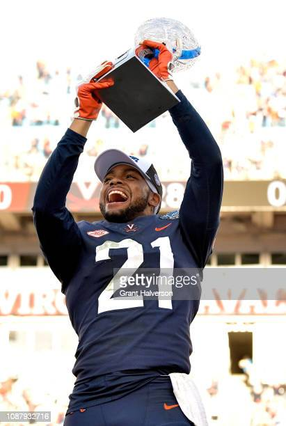 Juan Thornhill of the Virginia Cavaliers celebrates with the trophy after a win against the South Carolina Gamecocks during the Belk Bowl at Bank of...