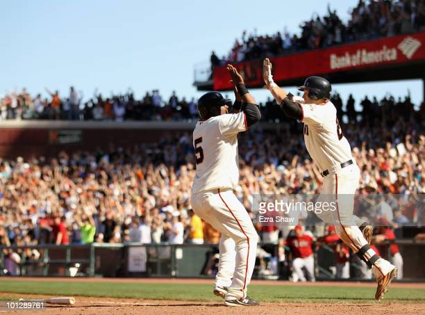 Juan Uribe is congratulated by Freddy Sanchez after Uribe scored the winning run on a single by Andres Torres of the San Francisco Giants in the 10th...