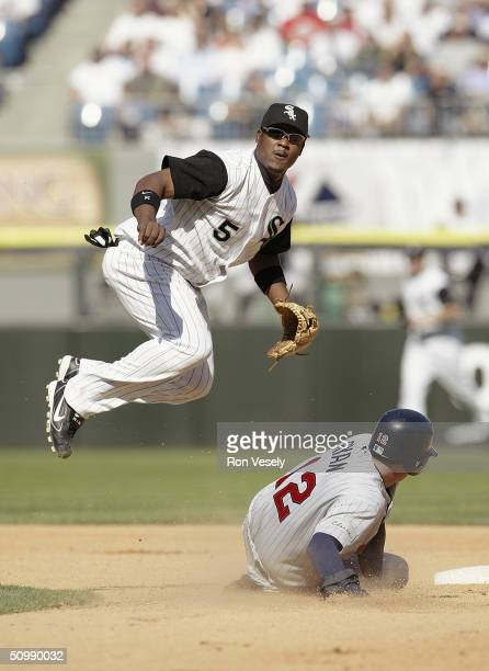 Juan Uribe of the Chicago White Sox follows through on a throw to first base for the double-play as Michael Ryan of the Minnesota Twins slides into...