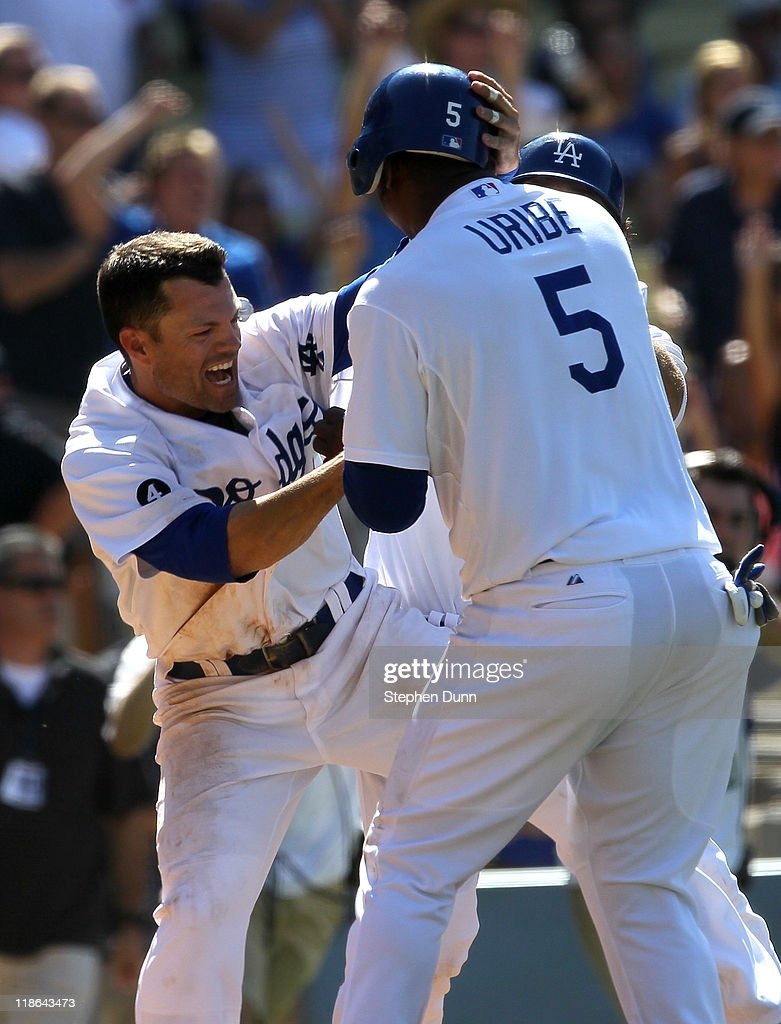 Juan Uribe #5 of the Los Angeles Dodgers celebrates with Jamey Carroll #14 after scoring the only run of the game with the San Diego Padres on a ninth inning two out walk off single by Dionaeer Navarro on July 9, 2011 at Dodger Stadium in Los Angeles, California. The Dodgers won 1-0.