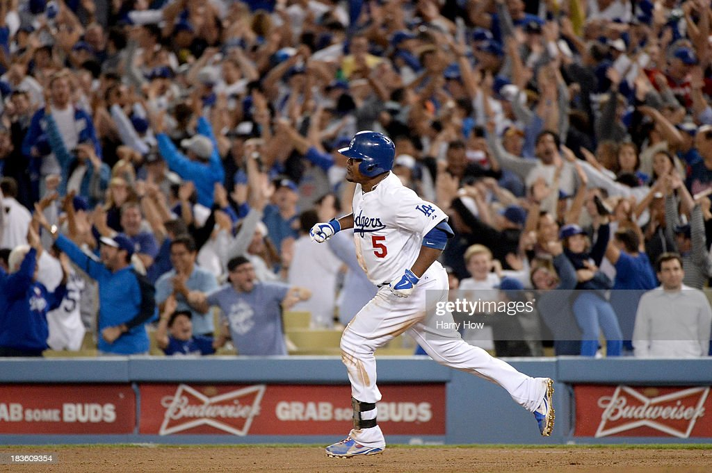 Juan Uribe #5 of the Los Angeles Dodgers reacts after he hits a two-run home run in the eighth inning against the Atlanta Braves in Game Four of the National League Division Series at Dodger Stadium on October 7, 2013 in Los Angeles, California.