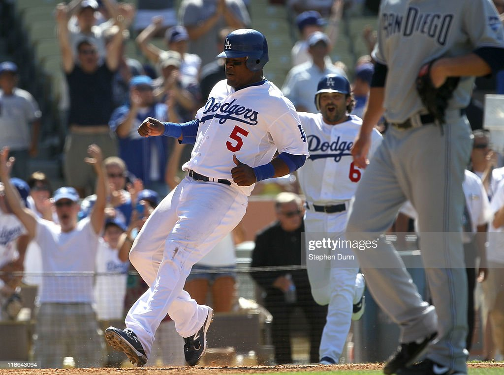 Juan Uribe #5 of the Los Angeles Dodgers scores the only run of the game with the San Diego Padres on a ninth inning two out walk off single by Dionaeer Navarro on July 9, 2011 at Dodger Stadium in Los Angeles, California. The Dodgers won 1-0.