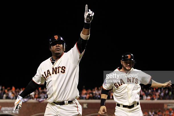 Juan Uribe of the San Francisco Giants celebrates with Cody Ross after hitting a three run homerun in the fifth inning against Darren O'Day of the...