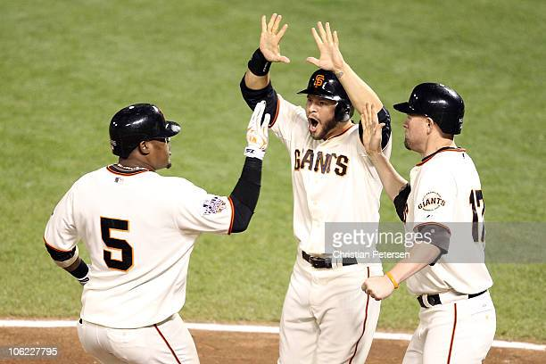 Juan Uribe of the San Francisco Giants celebrates with Cody Ross and Aubrey Huff after hitting a three run homerun in the fifth inning against Darren...