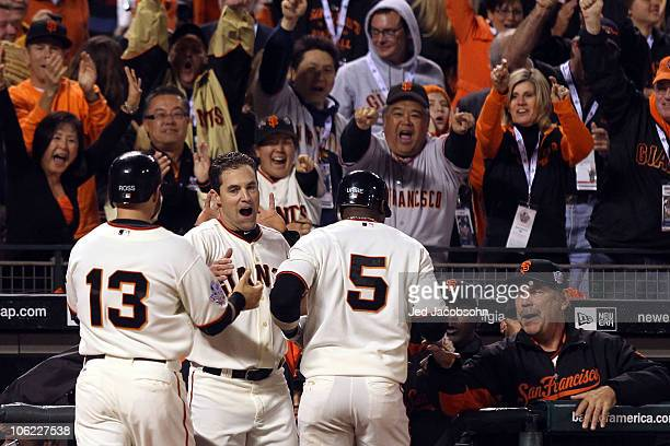 Juan Uribe of the San Francisco Giants celebrates with Cody Ross Pat Burrell and manager Bruce Bochy after hitting a three run homerun in the fifth...