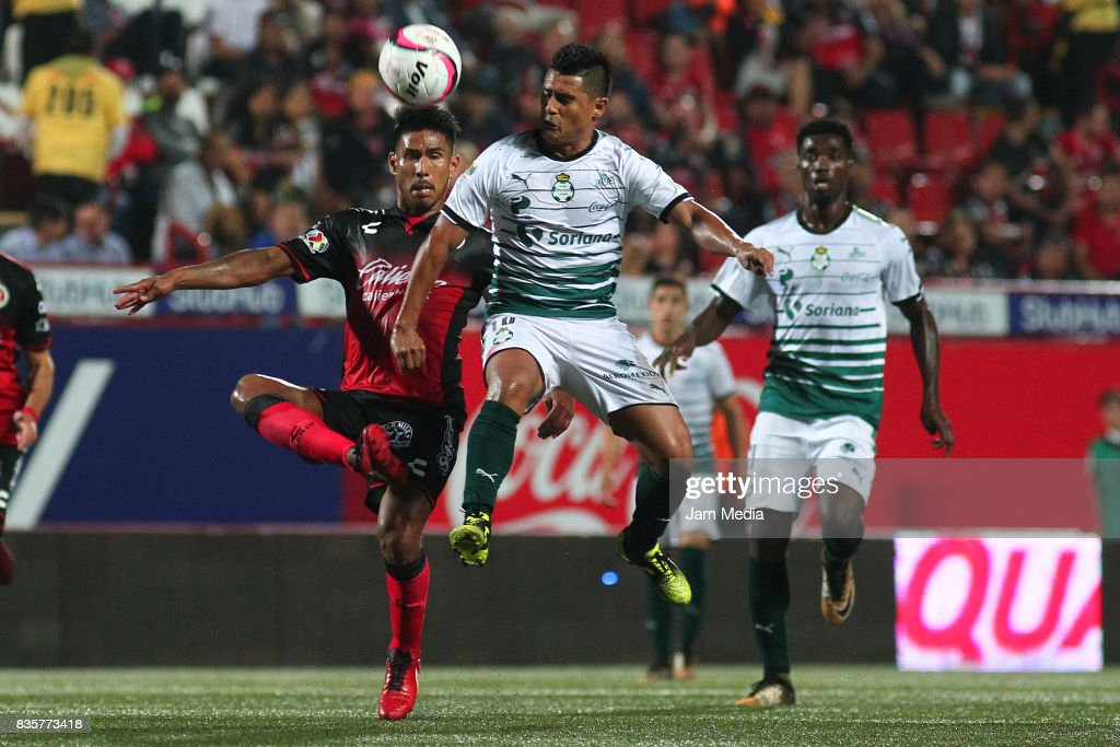 Juan Valenzuela (L) of Tijuana and Osvaldo Martinez (R) of Santos Laguna compete for the ball during the fifth round match between Tijuana and Santos Laguna as part of the Torneo Apertura 2017 Liga MX at Caliente Stadium on August 18, 2017 in Tijuana, Mexico.