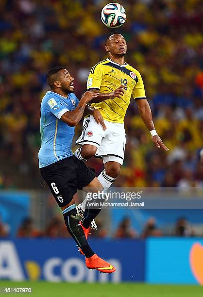 Juan Zuniga of Colombia in action against Alvaro Pereira of Uruguay during the 2014 FIFA World Cup Brazil round of 16 match between Colombia and...