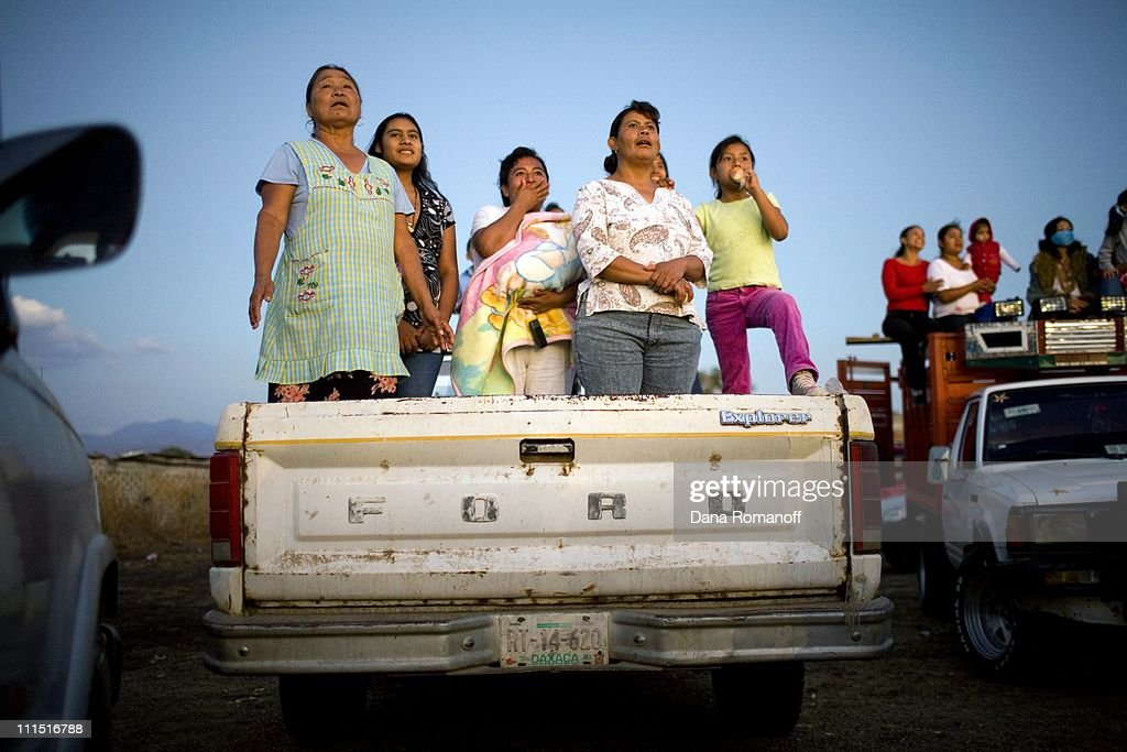 Juana Emilia Perez, (far left) and family watch her youngest son compete in a rodeo on February 17, 2008 in San Pablo Huixtepec. Of Juana's six children, five are in the United States. The annual rodeo used to be a big event. Now organizers have to invite cowboys from other Mexican villages to get enough competitors there aren't enough local men left. 80% of working-age men from town emigrate to the U.S. in search of work. Due to riskier and more costly border crossings, the migrants stay in the U.S. and do not come back home in fear that they will not be able to get back across the border. It's been 18 years since Juana saw one of her sons. 'When they boys turn 15, they go' says Juana. 'They don't come because they don't have papers. They are there so they can have something here in their town: to have land, a house, a truck and something for their family.'