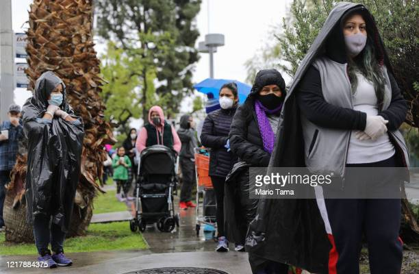Juana Gomez from North Hollywood wears a face mask and gloves while using a trash bag to protect against the rain as she waits in line to receive...