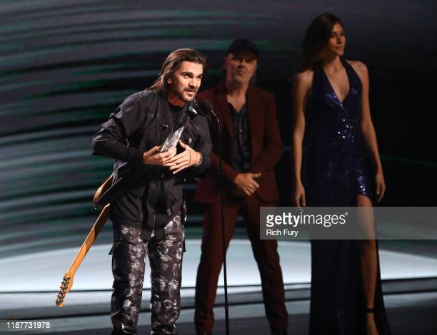 Juanes accepts his Person of The Year Award from Lars Ulrich onstage during the 20th annual Latin GRAMMY Awards at MGM Grand Garden Arena on November...