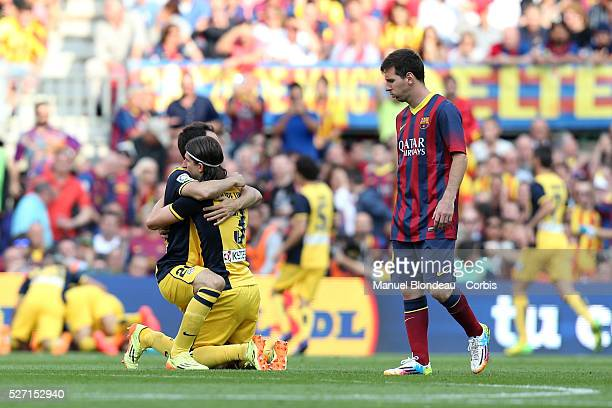 Juanfran and Filipe Luis of Club Atletico de Madrid celebrate as Lionel Messi of FC Barcelona looks dejected during the La Liga football match...