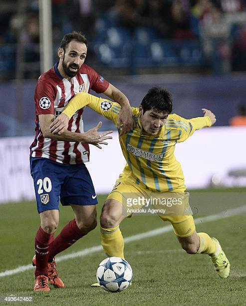 Juanfran of Atletico de Madrid competes for the ball with Yeldos Akhmetov of FC Astana during the UEFA Champions League Group C match between Club...
