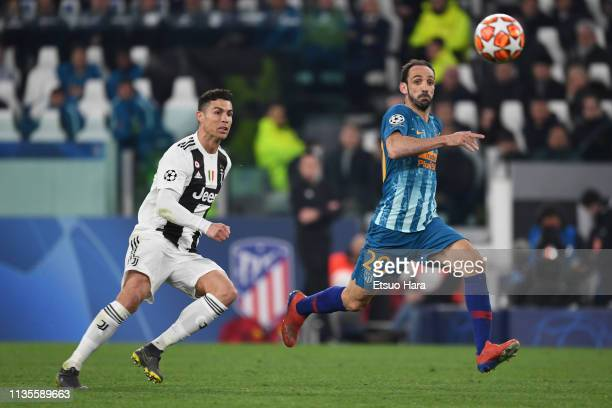 Juanfran of Atletico Madrid and Cristiano Ronaldo of Juventus compete for the ball during the UEFA Champions League Round of 16 Second Leg match...