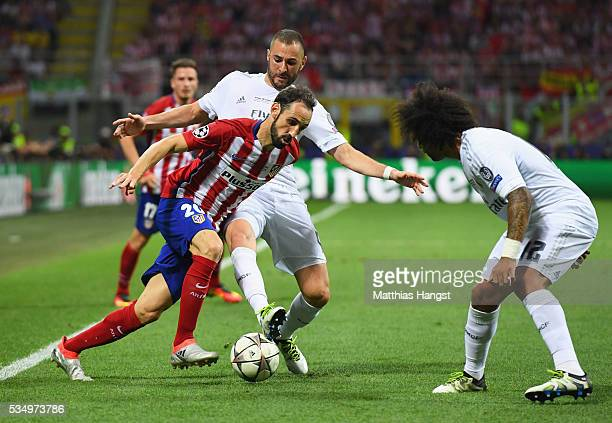 Juanfran of Atletico Madrid battles for the ball with Karim Benzema of Real Madrid during the UEFA Champions League Final match between Real Madrid...