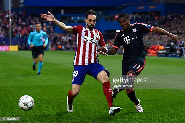 Juanfran of Atletico Madrid makes a challenge on Douglas Costa of Bayern Munich during the UEFA Champions League semi final first leg match between...