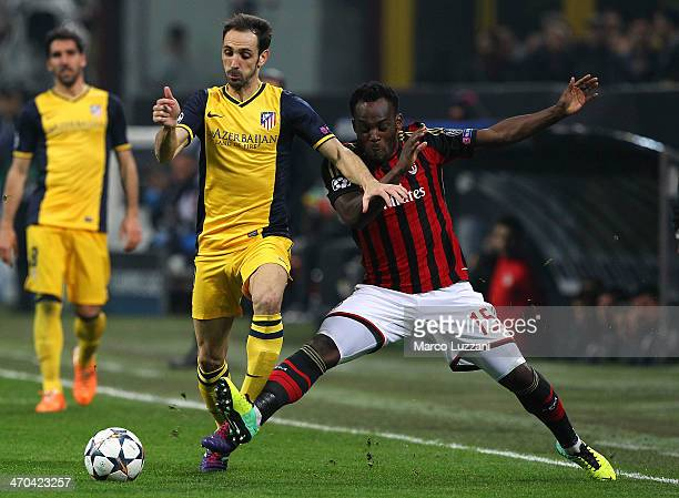 Juanfran of Club Atletico de Madrid competes for the ball with Michael Essien of AC Milan during the UEFA Champions League Round of 16 match between...