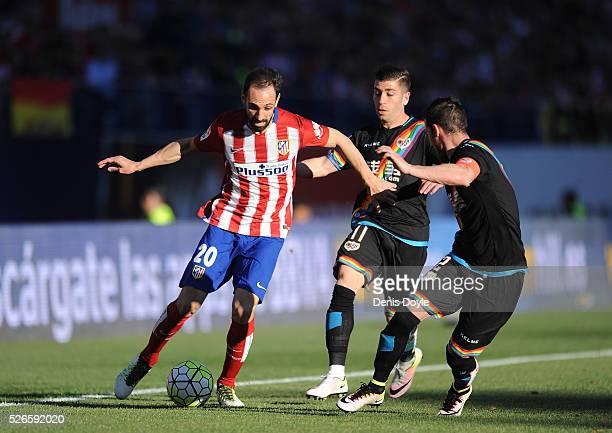 Juanfran of Club Atletico de Madrid ends off Adrian Embarba and Robrto Roman Triguero ����Tito���� of Rayo Vallecano de Madrid during the La Liga...