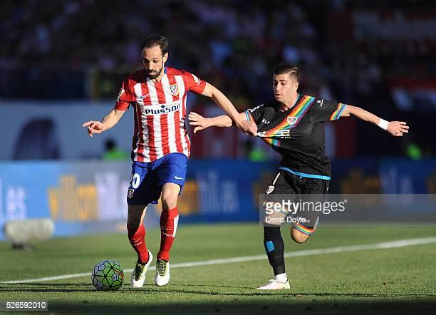 Juanfran of Club Atletico de Madrid ends off Adrian Embarba of Rayo Vallecano de Madrid during the La Liga match between Club Atletico de Madrid and...