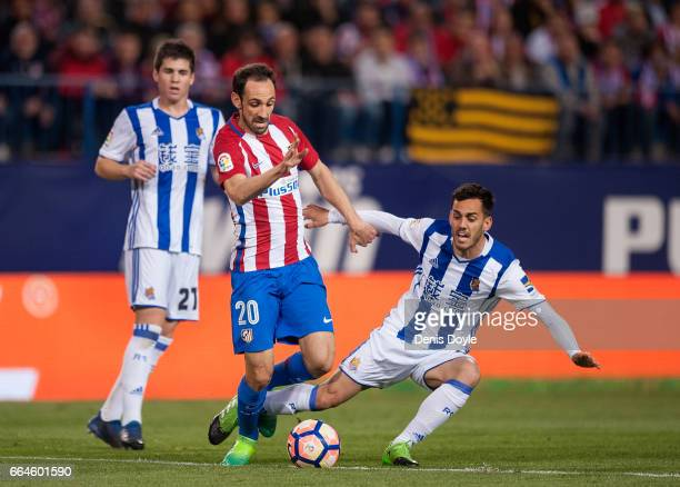 Juanfran of Club Atletico de Madrid is tackled by Inigo Martinez of Real Sociedad de Futbol during the La Liga match between Club Atletico de Madrid...