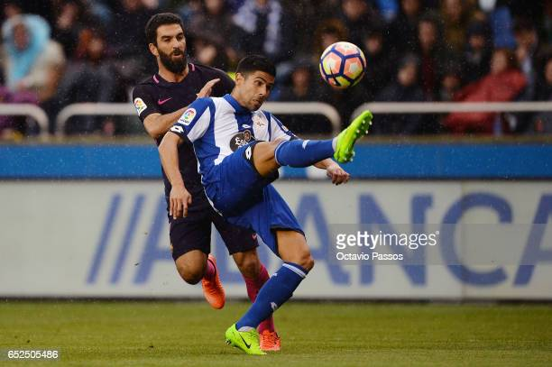 Juanfran of RC Deportivo La Coruna competes for the ball with Arda Turan of FC Barcelona during the La Liga match between RC Deportivo La Coruna and...
