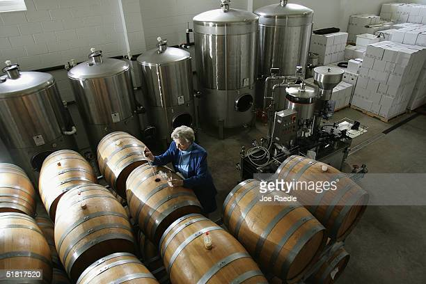 Juanita Swedenburg who runs Swedenburg Estate Vineyard a small family winery pulls a sample of wine from a barrel in her wine cellar December 2 2004...