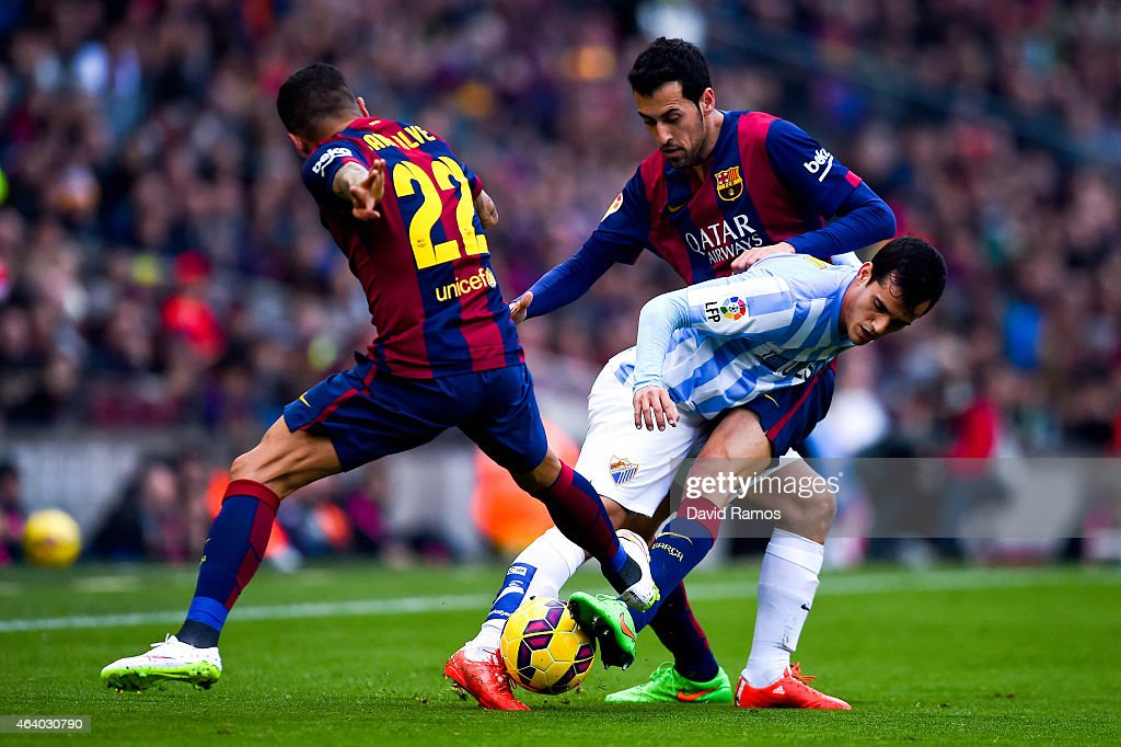 Juanmi Jimenez of Malaga CF competes for the ball with Sergio Busquets and Dani Alves of FC Barcelona during the La Liga match between FC Barcelona and Malaga CF at Camp Nou on February 21, 2015 in Barcelona, Spain.