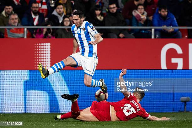 Juanpe Ramirez of Girona FC tackles Raul Navas of Real Sociedad during the La Liga match between Girona FC and Real Sociedad at Montilivi Stadium on...