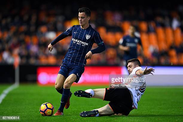 Juanpi Anor of Malaga CF competes for the ball with Guilherme Siqueira of Valencia CF during the La Liga match between Valencia CF and Malaga CF at...