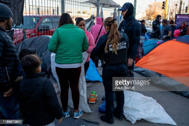 Juarez municipal police speak to asylum seekers camped out near Paso del Norte International Bridge trying to convince them to go to shelters for...