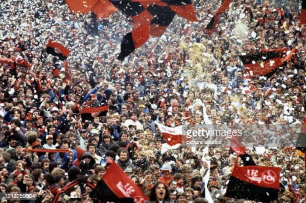 Jubelnde Fans des Fußballclubs 1. FC Nürnberg schwenken ihre Fahnen, zeigen ihre Fanschals mit den Farben ihres Vereins und werfen Konfetti und...