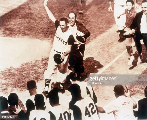 Jubilant American professional baseball player Bill Mazeroski of the Pittsburgh Pirates waves his hand as he walks across home plate to score the...