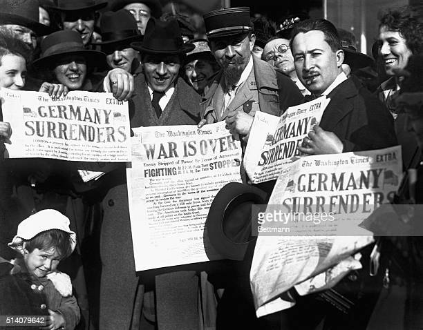Jubilant Americans in Washington, D.C., show newspaper headlines which announce the surrender of Germany, ending World War I, November 8, 1918.