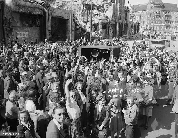 Jubilant Berliners. Berlin: Against a backdrop of war ruins, Berlin citizens gather around a mobile loudspeaker of the American Radio Station Berlin...