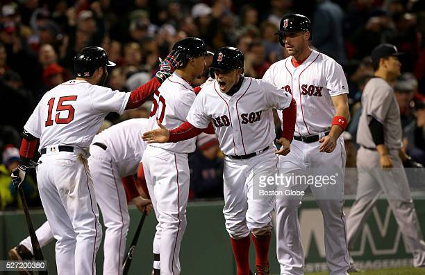 Jubilant Boston Red Sox left fielder Brock Holt celebrates at home plate after scoring the tying run on a 2 RBI double by Boston Red Sox center...