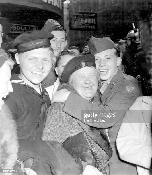 Jubilant civilians and military personnel among them an elderly English woman and two American servicemen gather at Piccadilly Circus to celebrate...