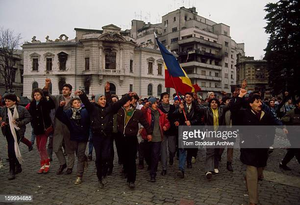 Jubilant demonstrators wave the Romanian flag as they march through the streets towards Palace Square afterwards named Revolution Square during the...