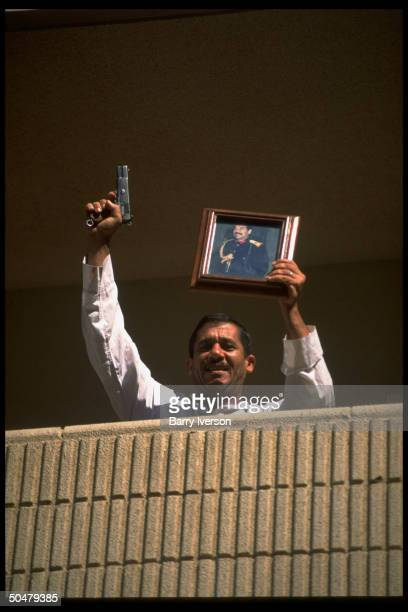 Jubilant Iraqi holding pic of Saddam Hussein firing pistol into air fr his housing block balcony feting Pres's big win in 1cand election yes or no...