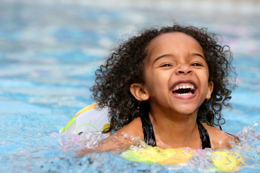 A jubilant kid swimming in a pool 147038986