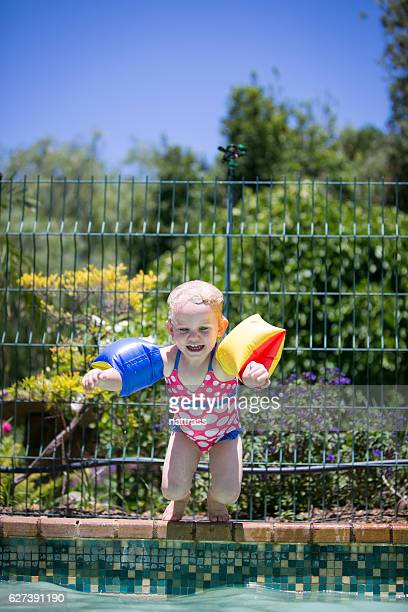 A jubilant little girl jumping into a swimming pool