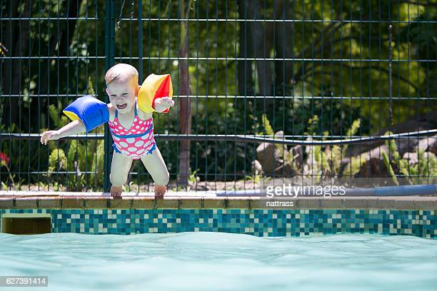 Jubilant little girl jumps into the swimming pool